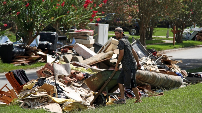 A resident cleans up Aug. 20 after the floods in Baton Rouge. (Photo: Shutterstock)