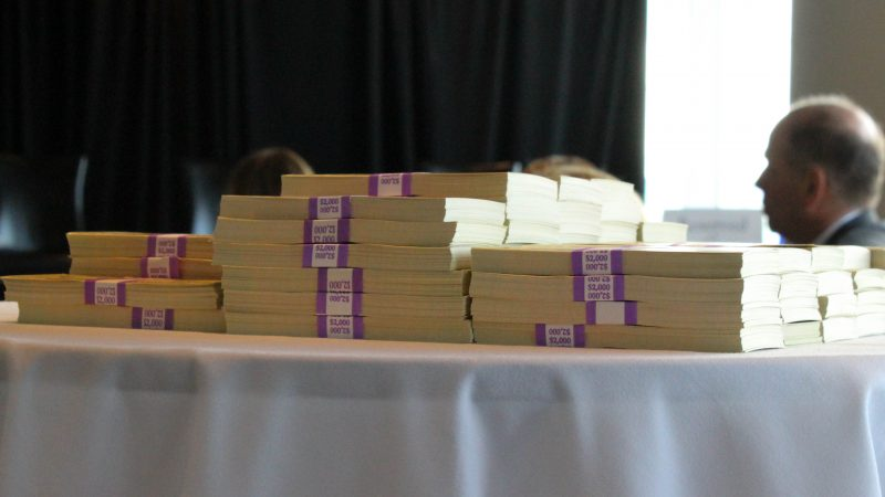 A pile of fake money representing the $150,000 spent on the FedRAMP dashboard was presented as an example of agency spending waste. (Photo: MeriTalk)